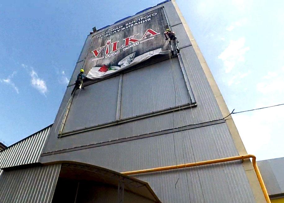 Процесс монтажа баннера на подготовленную конструкцию
